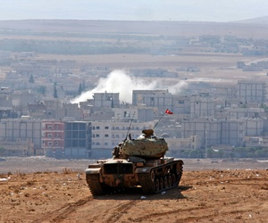 Turkish soldiers hold their position in a tank on the outskirts of Suruc, at the Turkey-Syria border, near the town of Kobani.