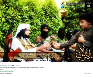 This Screen grab from an Islamic State affiliated Twitter account, taken Sept. 20, 2014, purports to show senior military commander Abu Wahib handing a flower to a child while in southern Iraq, as part of the group's broad social media campaign.