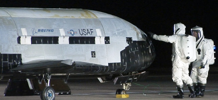 Air Force personnel conduct checks on the X-37B vehicle after a landing at Vandenberg Air Force Base, on December 3, 2010.