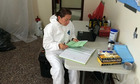A lieutanent with the Naval Medical Research Center reviews documentation at a mobile laboratory in Bushrod Island, Liberia.