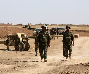 Kurdish peshmerga forces stand by their vehicles after they take control of a village from ISIS fighters, on October 1, 2014.
