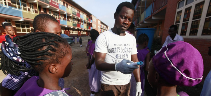 A teacher at the Adekunle primary school in Lagos, Nigeria, uses a thermometer to test the temperature of students, on October 8, 2014.