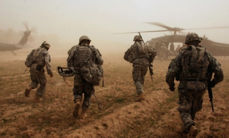 Soldiers with the 101st Airborne Division run to UH-60 Blackhawk helicopters after conducting a search for weapons caches in Albu Issa, Iraq.