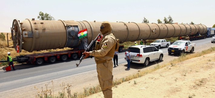 A Kurdish peshmerga fighter stands guard as new equipment arrives at the Kalak refinery on the outskirts of Irbil, Iraq.