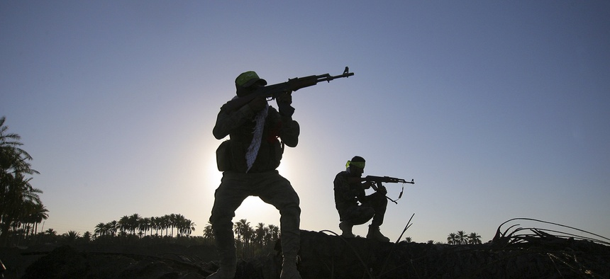 Iraqi Shiite fighters aim their weapons during clashes southwest of Baghdad, Iraq, on October 7, 2014.