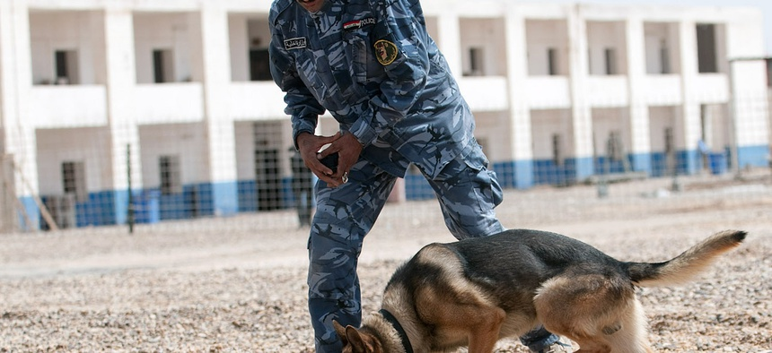 An Iraqi dog handler in Ramadi trains a German shepherd to find explosive samples.