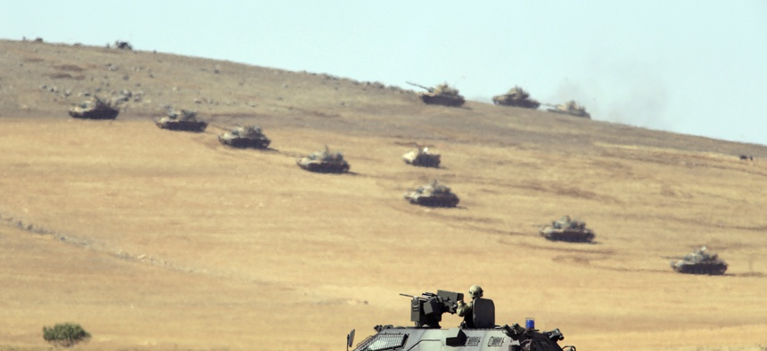 Turkish tanks and armored vehicles hold their positions on a hilltop outside of Suruc, at the Turkey-Syria border, on October 6, 2014.