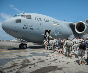 A group of 30 U.S. military personnel, including Marines, Airmen, and Soldiers from the 101st Airborne Division, board a C-17 in Senegal en route to Liberia.