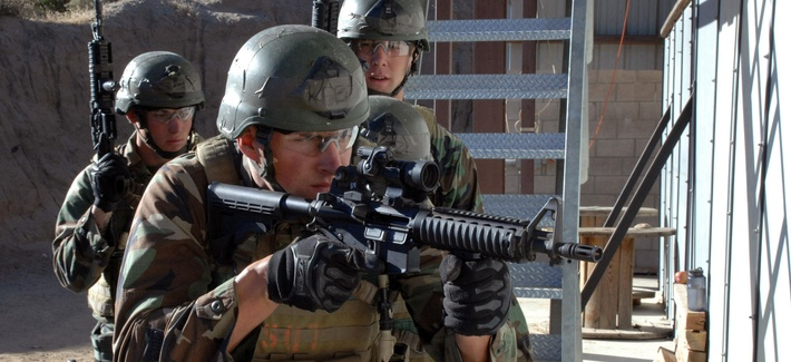 A team of four SEAL trainees prepare to breach a room during a training exercise.