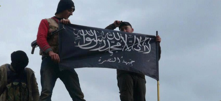 Militants with the Al-Qaeda affiliated Jabhat al-Nusra wave their flag on top of a Syrian air force helicopter at Taftanaz air base, in Idlib, Syria.