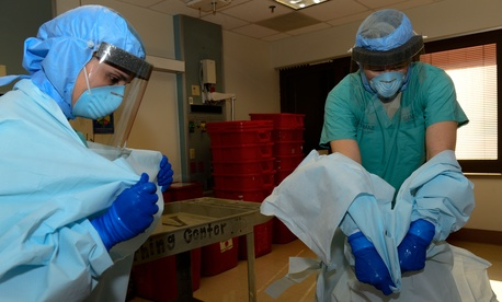 Two Army officers take off their protective personal equipment while training for Ebola response operations at the San Antonio Military Medical Center, on October 23, 2014.