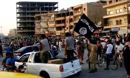 This file photo posted by the Raqqa Media Center, a Syrian opposition group, on Monday, June 30, 2014, which has been verified and is consistent with other AP reporting, shows fighters from extremist Islamic State group during a parade in Raqqa, Syria.