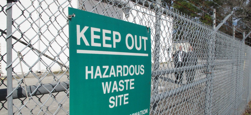 """In a Feb. 27, 2013 file photo, a sign cautions visitors outside a """"pump and treat"""" facility on the Marine base at Camp Lejeune, N.C. The sprawling installation is the site of one of the worst drinking water contaminations in U.S. history."""