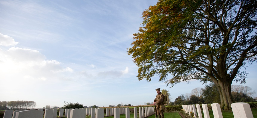 Re-enactor Chris Barker looks at gravestones during a re-burial ceremony for 15 World War I soldiers in Bois-Grenier, France, Oct. 22, 2014. Fifteen British WWI soldiers were re-buried at Y Farm Commonwealth cemetery nearly a century after they perished.