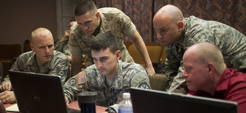 """A Naval Academy professor works with his teammates at the Army's Cyber Center of Excellence at Fort Gordon during """"NetWar,"""" on June 10, 2014."""