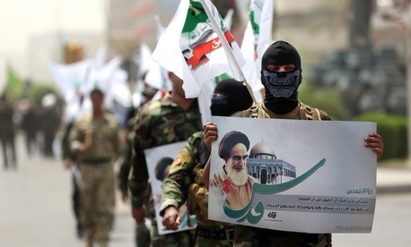 Supporters of Iraqi Hezbollah brigades march in military uniforms with a portrait of Iran's supreme late Iranian leader Ayatollah Khomeini during a parade marking Quds Day, on July 25, 2014.