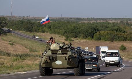 A Russian military vehicle maneuvers on a road behind an aid convoy of trucks, 15 kilometers (9 miles) from the Ukrainian border in the Rostov-on-Don region, Russia, on Aug. 15, 2014.