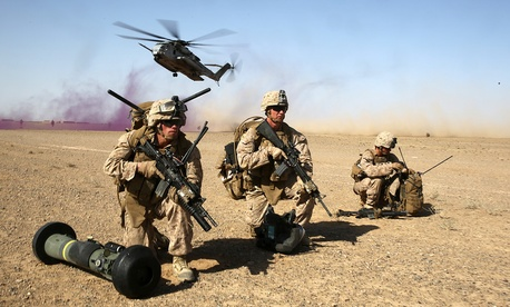 A group of Marines provide security as a CH-53 Super Sea Stallion helicopter lands during a mission in the Helmand Province, on April 28, 2014.
