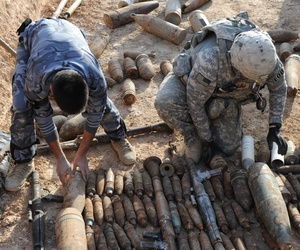 An Army sergeant arranges unexploded ordnance for dispoal at a site in Ramadi, Iraq.
