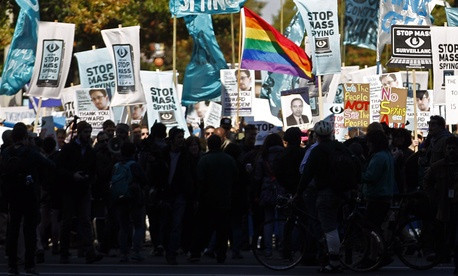 Demonstrators march through Washington towards the U.S. Capitol to rally and demand that the Congress investigate the National Security Agency's mass surveillance programs.