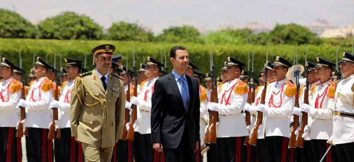 Syria's President Bashar Assad reviews an honor guard upon his arrival at the presidential palace, in Damascus, Syria, on July 16, 2014.