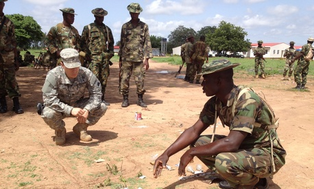 A California National Guard Special Forces soldier reviews a sand table map with a Nigerian soldier in Nigeria.
