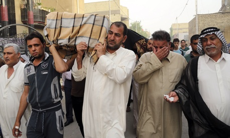 Friends and family members of a suicide bombing attack grieve as they carry the coffins near the site of an attack, on October 12, 2014.