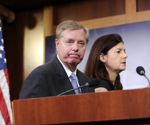 Sen. Lindsey Graham, R-S.C., and Sen. Kelly Ayotte, R-N.H., walks off the stage following a news conference on Capitol Hill, on July 24, 2014.