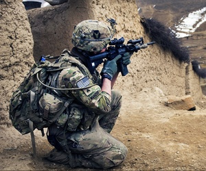 An Army sergeant scans a nearby mountain range during a search of Qual-e Jala village in Afghanistan.
