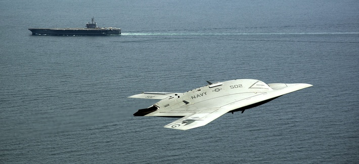 An X-47B demonstrator flies near the USS George H.W. Bush.
