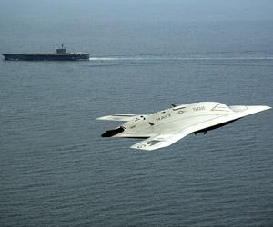 An X-47B demonstrator flies near the USS George H.W. Bush.