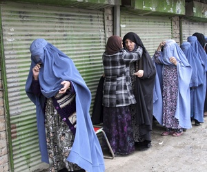 An Afghan woman searches voters before they enter polling station to cast ballots on April 4, 2014.