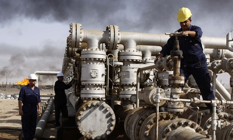 Iraqi laborers work at the Rumaila oil refinery near the city of Basra, Iraq, on December 13, 2009.