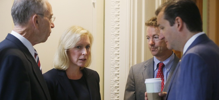 Sen.s Chuck Grassley, R-Iowa, Kirsten Gillibrand, D-N.Y., Rand Paul, R-Ky., and Ted Cruz, R-Texas., huddle before a news conference on Capitol Hill.