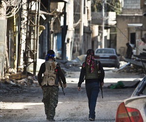 Kurdish fighters walk near the town entrance circle in route to their strongholds in Kobani, Syria, on November 19, 2014.