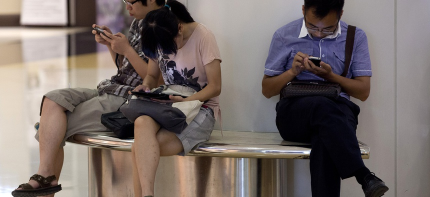 People sit on a bench inside a shopping mall using their tablet computer and smartphone in Beijing, China Monday, Aug. 19, 2013.