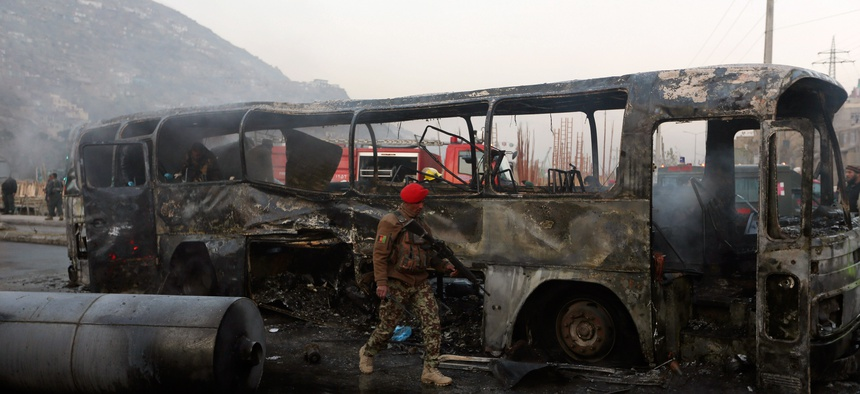 An Afghan soldier inspects a damaged bus at the site of a suicide attack by the Taliban in Kabul, Afghanistan, Saturday, Dec. 13, 2014.