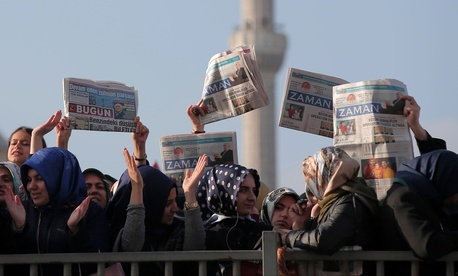 Women hold opposition newspapers as people gather outside the Justice Palace in Istanbul, Turkey, Dec. 14, 2014 to protest against the latest detentions in Turkey.