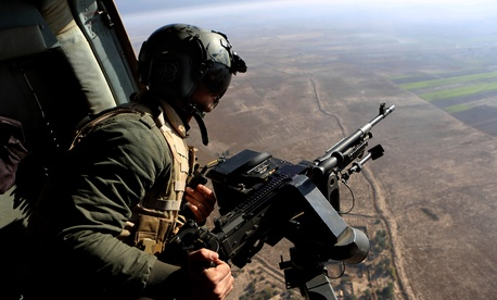 An Iraqi soldier secures an area from an helicopter carrying Iraqi Defense Minister Khalid al-Obeidi.