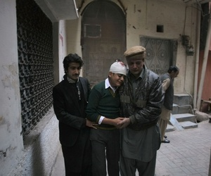 The uncle and cousin of an injured student comfort the boy as he mourns the death of his mother, who was a teacher at the military-run school that was attacked by the Taliban, on December 16, 2014.