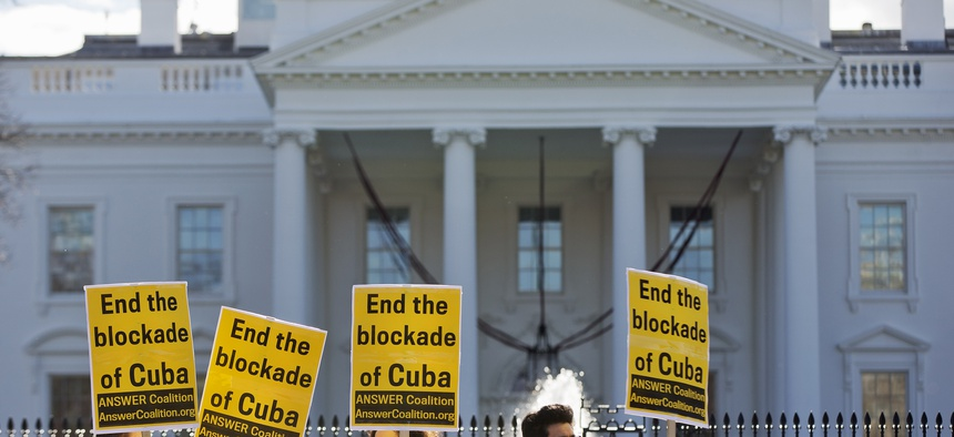 """People from the ANSWER Coalition hold signs urging the U.S. to """"End the blockade of Cuba,"""" during a demonstration outside of the White House on Decmeber 17, 2014."""