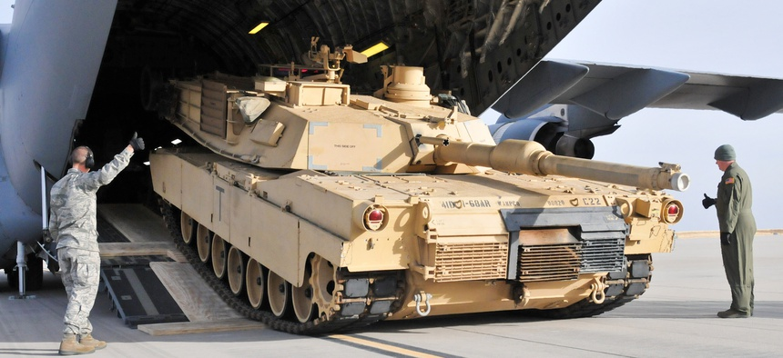Soldiers from the 4th Infantry Division offload an M1A2 Abrams battle tank from a plane at Fort Carson, on January 13, 2014.