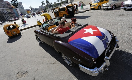 Tourists take a ride in a classic American convertible car with the Cuban national flag painted on the trunk, on December 18, 2014.