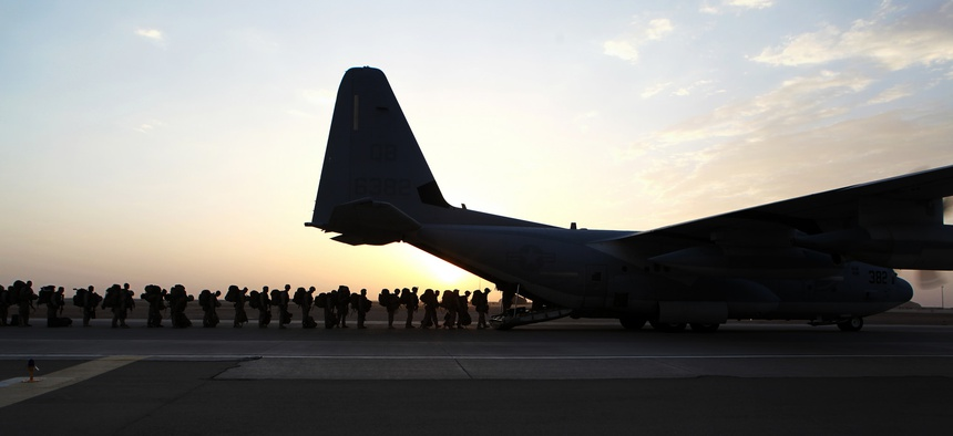 Troops with the Marine Expeditionary Brigade load onto a KC-130 aircraft onto the Camp Bastion flightline, on October 27, 2014.