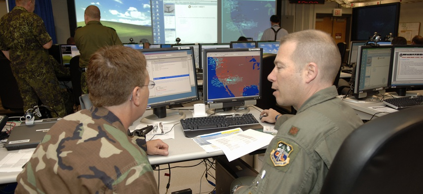 Airmen participate in a coalition nation demonstration inside a facility that works on cyber defense.