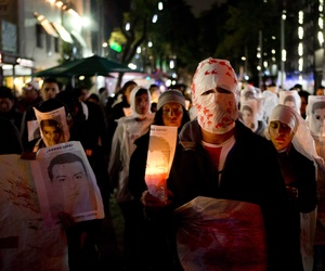 Demonstrators hold candles and images of some of the 43 students who were disappeared, in Mexico City, Friday, Nov. 14, 2014. The 43 teachers-school students disappeared at the hands of a city police force on Sept. 26 in the town of Iguala.