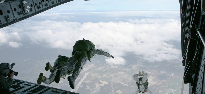 Members of the U.S. Army Special Forces soar out of the back of a C-17 during a HALO training exercise.