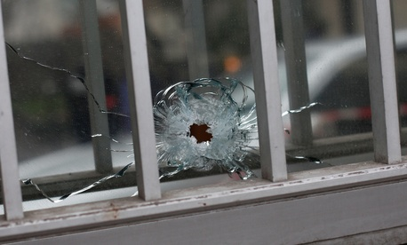 A bullet impact is seen in a window of a building next to the French satirical newspaper Charlie Hebdo's office, in Paris, Wednesday, Jan. 7, 2015.