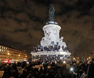 People gather around and on top of the Republique Plaza statue during the solidarity demonstration in Paris, Thursday, Jan. 8, 2015.