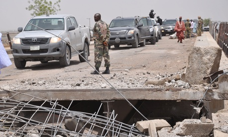 Soldiers and government officials inspect a bridge linking Nigeria and Cameroon following an attack by Islamic militants in Gambaru, Nigeria.